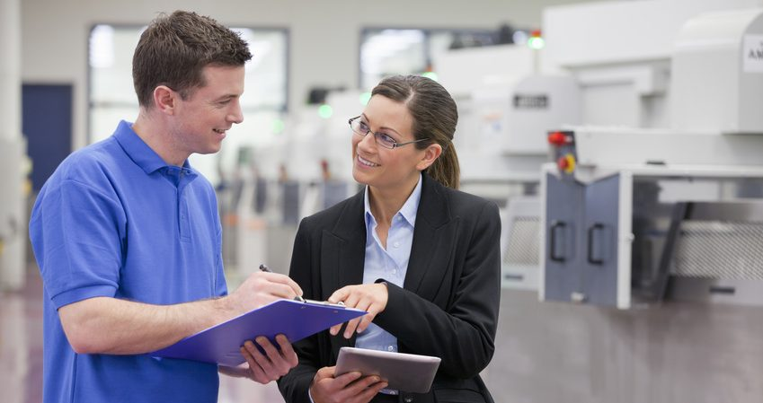 Smiling technician and businesswoman with clipboard in hi-tech manufacturing plant